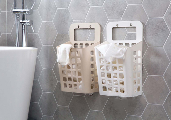 fix stylish laundry baskets on an empty wall